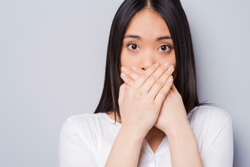 woman covering mouth with hands