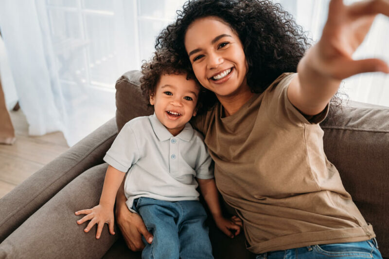 Young woman and her little son taking selfie