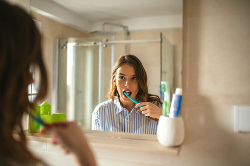 Portrait of a beautiful woman brushing teeth