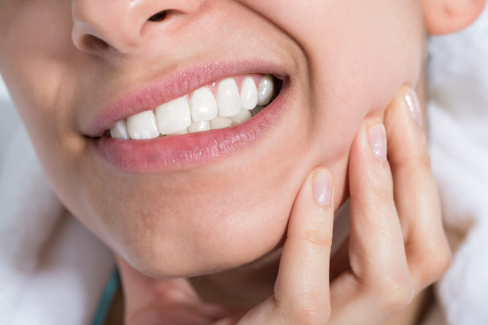 young woman suffering from toothache at home