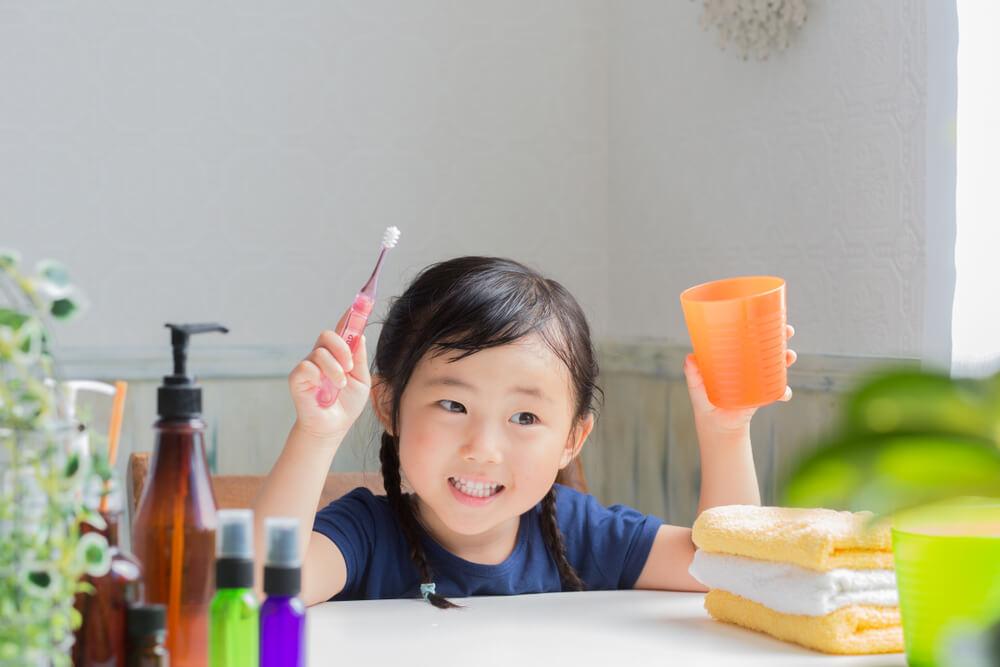 asian little girl brushing teeth