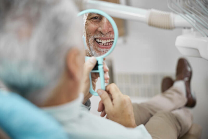 Aged patient sitting in a dental chair looking in the mirror