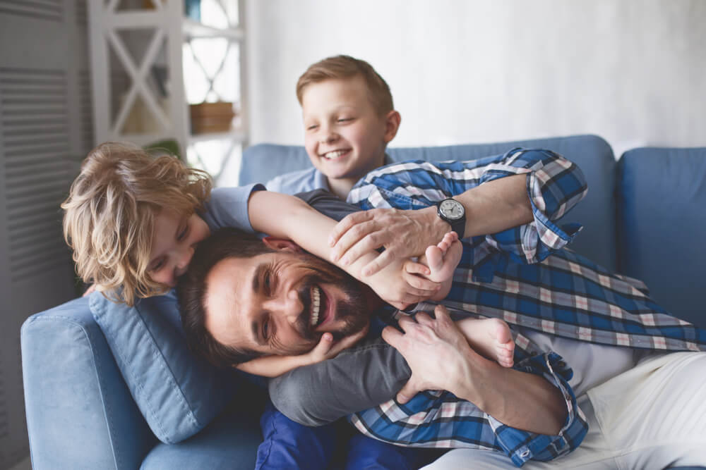 Smiling father and sons having fun on cozy couch