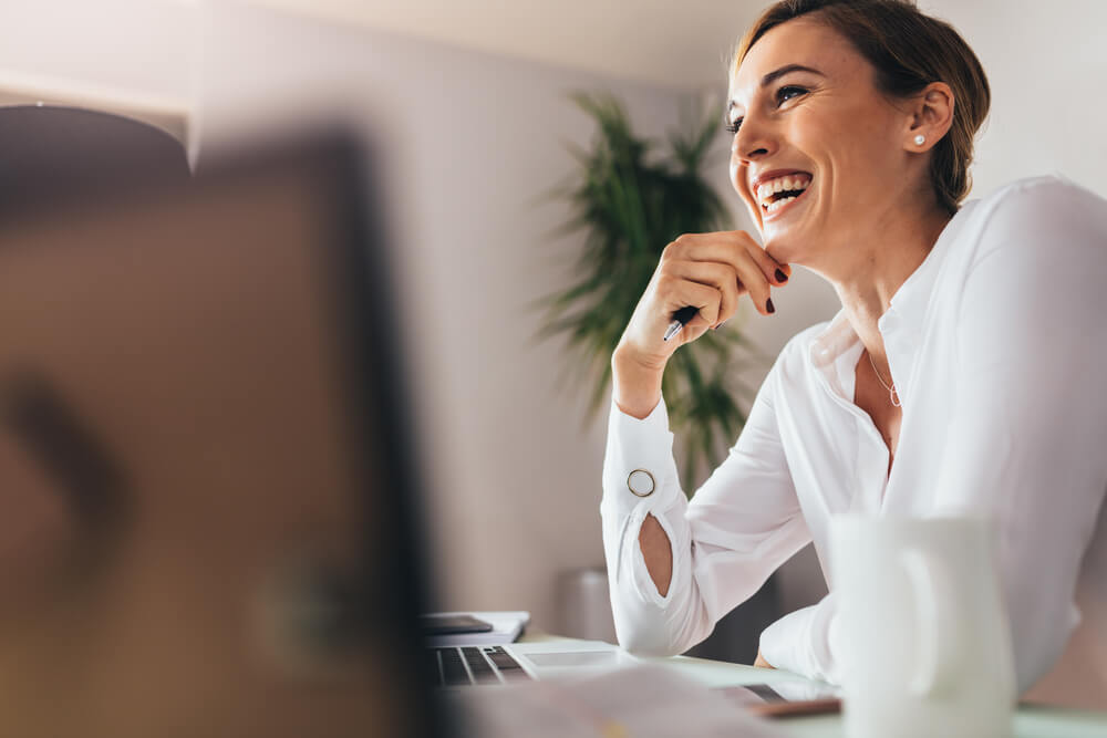 Smiling woman sitting at her desk in office